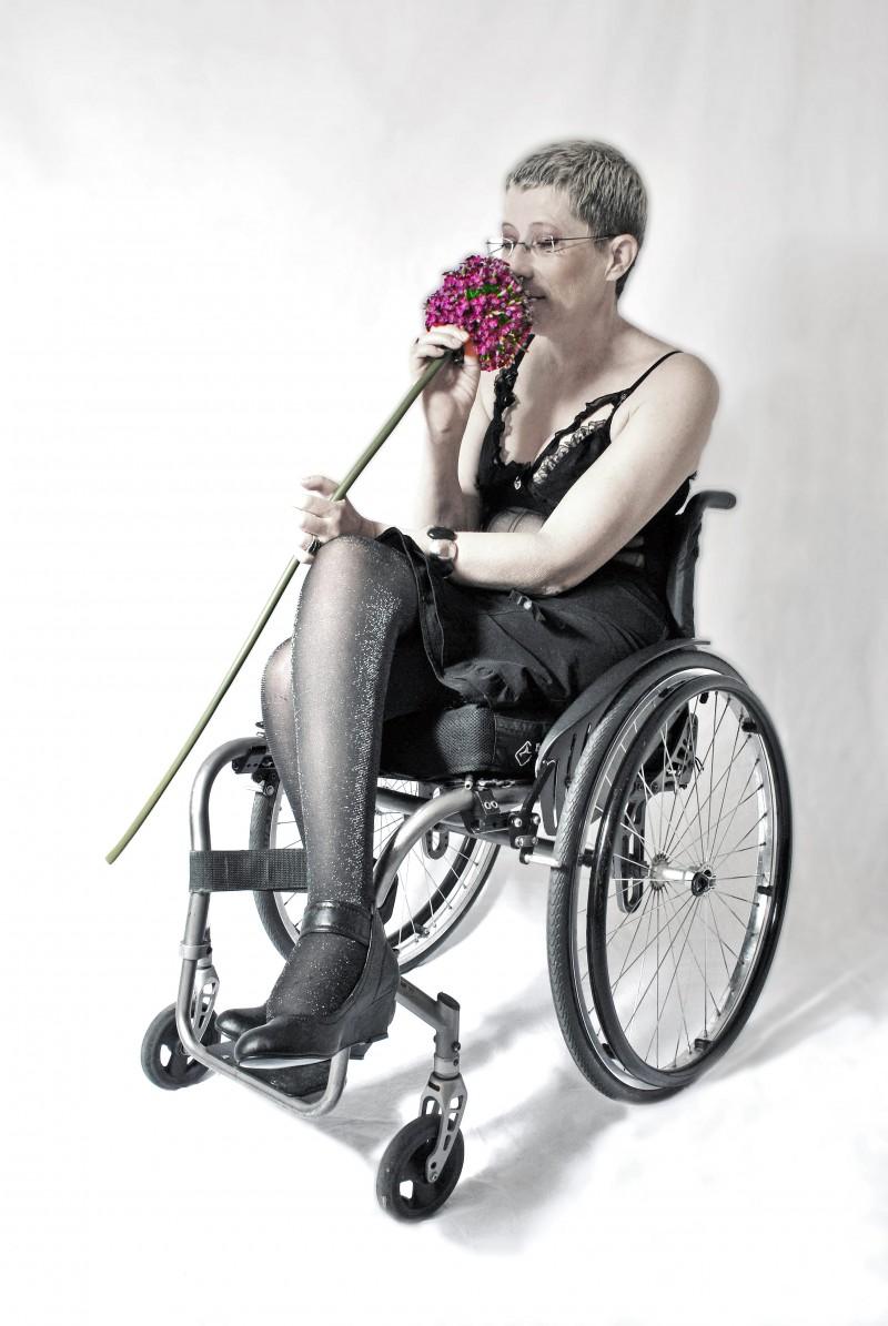Femme cheveux courts tétraplégique en fauteuil roulant sent une fleur rose